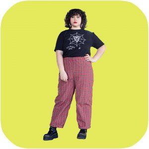 chica posando con una camiseta negra que tiene dibujada una telaraña con un insecto atrapado y se lee el amor no duele en inglés