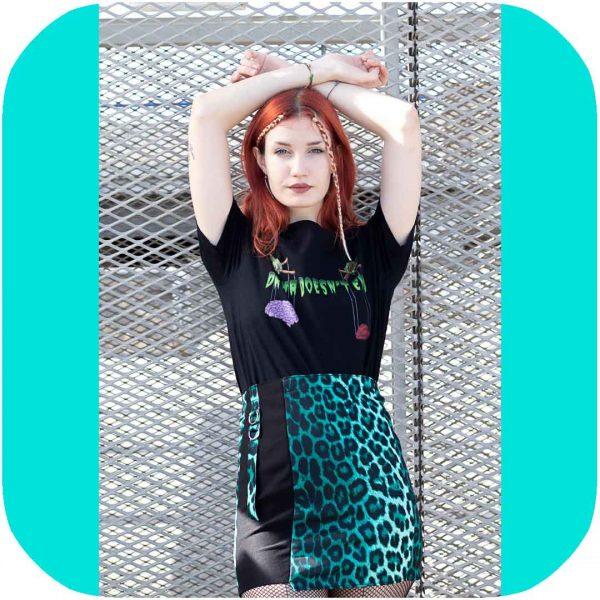 modelo posando con la falda con los brazos hacia arriba contra una valla