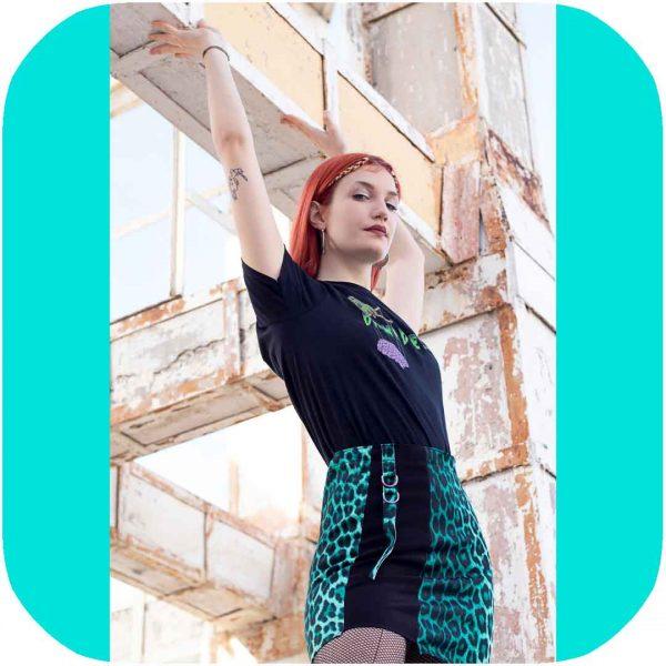 modelo posando con la falda con los brazos hacia arriba sosteniendo un pilar