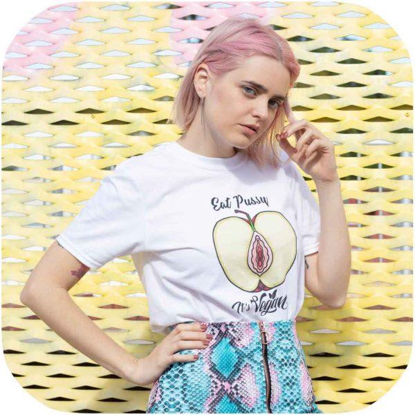 modelo posando con una camiseta blanca con una manzana cortada a la mitad que pone eat pussy, it's vegan