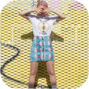 modelo posando con falda de serpiente rosa y turquesa